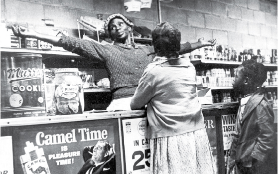Woman standing behind the counter of a cooperative market.