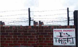 brick wall with barbed wire on top and a sign that has been grafittied to read Private Property is Theft