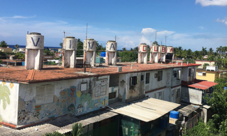 "Habana rooftops with water tanks that have ""Viva Cuba"" painted on them"