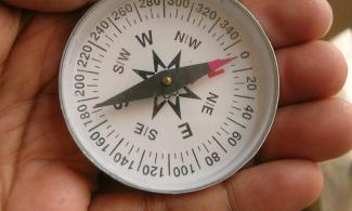 Hand holding a compass with needle aligned North and South.
