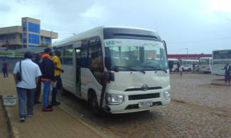 A bus from the Remera Transport Co-operative picking up passengers.