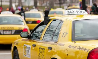 Line of Union Cabs at a protest. A driver is holding a raised fist out of their window.