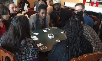People sitting around a table, playing the card game Loud and Proud.