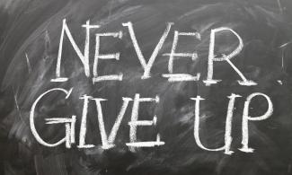 "Chalk board reading ""never give up"""