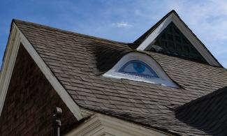 Gable on the roof of a house painted to look like an eye.