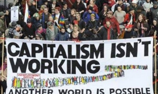 "Protesters from Occupy Wall Street holding a banner that reads ""capitalism isn't working."""