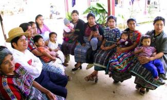 Mayan women and their children sit and listen to a presentation.